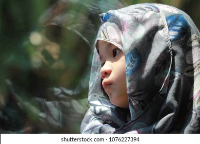 Portrait of 5 year old Asian Muslim little girl waering hijab or headscarf sit by the window.Girl look sad or scare or feel bad.Concept of sad,lonely