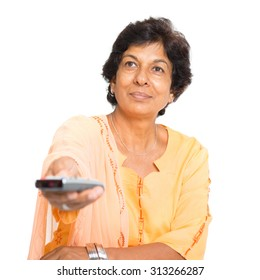 Portrait of a 50s Indian mature woman watching tv and hand holding remote control changing channel, isolated on white background.