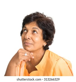 Portrait of a 50s Indian mature woman smiling and looking up having a thought, isolated on white background.
