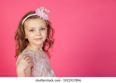 Portrait 5-6 year old girl in dress on pink isolated background looks at camera. Concept Playing and Children Recreation. Little child in casual clothes posing and showing emotions. Copy space
