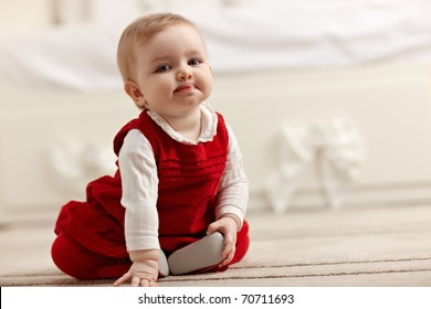 portrait of 6 months female child sitting on floor in red clothes and looking at camera. Horizontal shape, front view, copy space