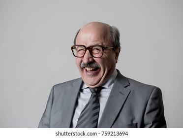 portrait of 60s bald senior happy business man gesturing funny and comic in laughter and fun face expression looking happy and cheerful isolated on grey background
