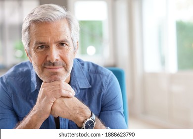Portrait of 60-year-old man with grey hair and blue shirt looking at camera