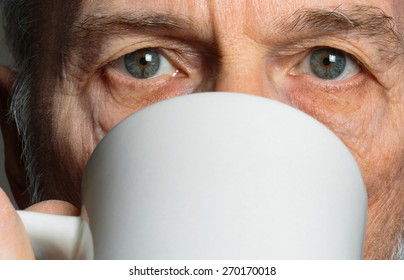 Portrait of 65-year-old Caucasian man drinking coffee from a white mug.