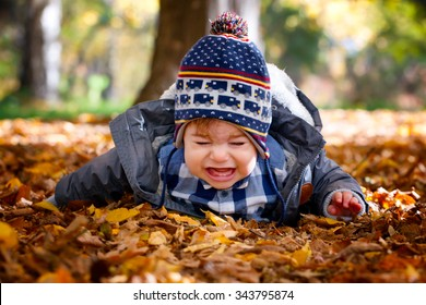 Portrait of 8 months old baby boy crying outdoors.