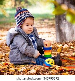 Portrait of 8 months old baby boy enjoying a fall day in the park between trees and leaves.