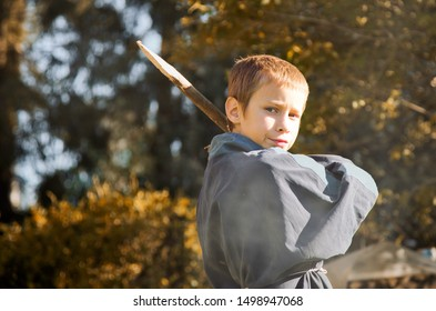 Portrait of a 8 year boy with a wooden stake in his hands.