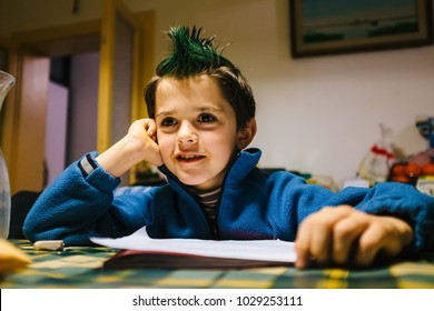 portrait of 9 year old boy at home with crest of green colored hair