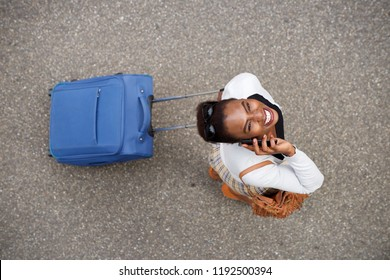 Portrait from above of happy african american woman walking with travel bag and mobile phone