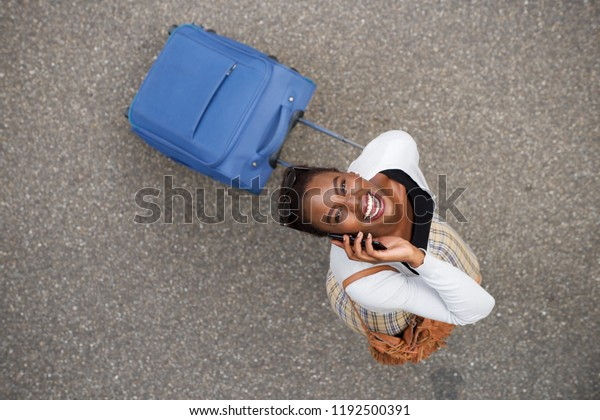 Portrait from above of happy african american woman walking with suitcase and mobile phone