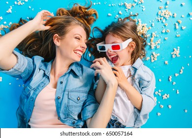 Portrait from above happy time together of beautiful mother having fun with daughter on blue floor. Laying in popcorn, enjoying family happiness, expressing true positive emotions