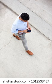 Portrait from above of man walking and using mobile phone