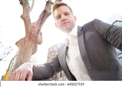 Portrait of achiever smart and elegant business man against flare sunny sky in financial city district, confident, looking to camera outdoors. Slick suited professional male, aspirational lifestyle.