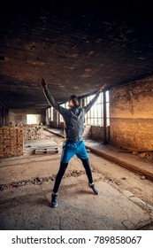 Portrait of active afro-american young attractive athletic man with earphones stretching and warming up before workout inside of the abandoned place with open arms.
