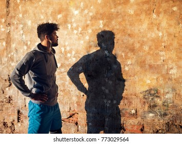 Portrait of active afro-american young handsome athletic man with earphones looking in his silhouette on the wall outside on a sunny day. Defeat yourselfe.
