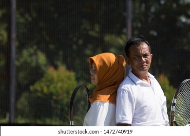 Portrait of an active asian muslim senior couple standing at outdoors tennis hard court and ready to play tennis. at sunny days