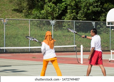 Portrait of an active asian muslim senior couple standing at tennis hard court and ready to play tennis. senior man teach woman how to swing tennis racket