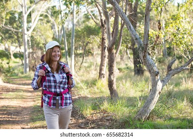 Portrait active attractive mature woman hiking happy and relaxed with backpack in the woods, Australian nature blurred background.