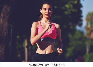 Portrait of active brunette hair woman running in the park in early morning. Young female runner training outdoors. Jogger in action