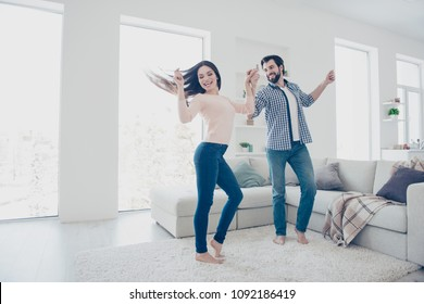 Portrait of active cheerful couple in casual outfits dancing singing indoor, in modern open space living room enjoying time together