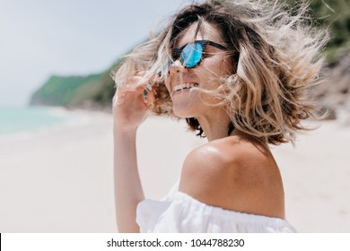 Portrait of active funny girl with short hairstyle walks down on the ocean with flying hair at camera and charming smile. Real emotions, background beach with white sand and rocks