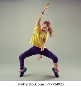 Portrait of active girl performing aerobics dance over grey background.  Sport and leisure concept.