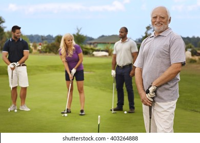 Portrait of active happy senior on the golf course, people playing at the background.