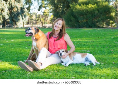 Portrait active mature woman with her dogs in park, sitting relaxed on green grass, cuddling pets, copy space.
