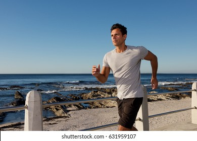 Portrait of active middle age man jogging outside by sea