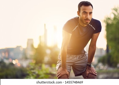 Portrait of active millenial man jogging at dusk with an urban cityscape and sunset in the background