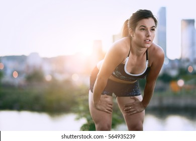 Portrait of active millenial woman jogging at dusk with an urban cityscape and sunset in the background