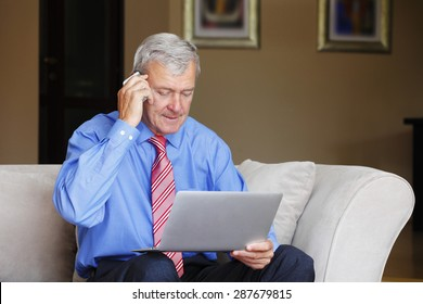 Portrait of active retired man sitting at home and working. Senior businessman using his laptop while making call.