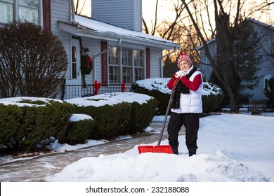 Portrait of Active Senior Citizen with Snow Shovel in Front of Home