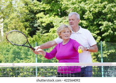 Portrait of  an active senior couple standing at tennis court and ready to play tennis.