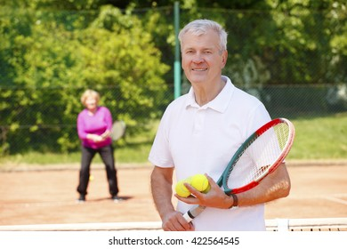 Portrait of an active senior man standing at tennis court and holding in hands tennis racket while elderly woman ready to play tennis at background.