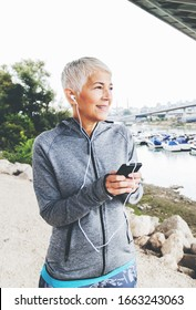 Portrait Of Active Senior Running Woman Listening Music With Smartphone , Workout Outdoor.