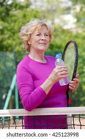 Portrait of active senior tennis trainer woman drinking a bottle of water while standing at net on tennis court.