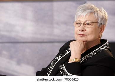 Portrait of active senior woman in smart clothes, thinking.?