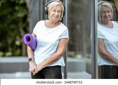 Portrait of an active senior woman in sports clothes standing with yoga mat near the building outdoors. Concept of a healthy lifestyle on retirement