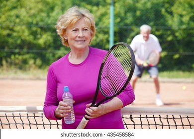 Portrait of active senior woman standing at tennis court while holding in her hand a tennis racket and a bottle of mineral water.
