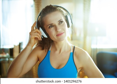 Portrait of active sports woman in sport clothes listening to the music with headphones in the modern house.