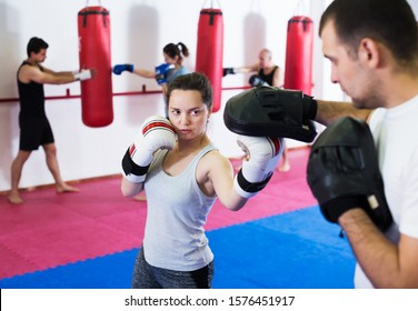 Portrait of active sportswomen competing in colored boxing gloves