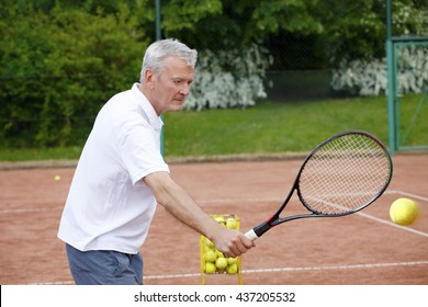 Portrait of active tennis trainer serving tennis ball.