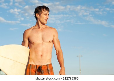 portrait of an active young man standing with a surfboard at the beach