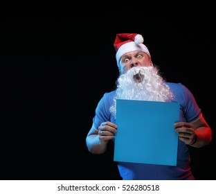 portrait actor male in cap and beard of Santa Claus with a sheet of paper for notes in the hands on a black background