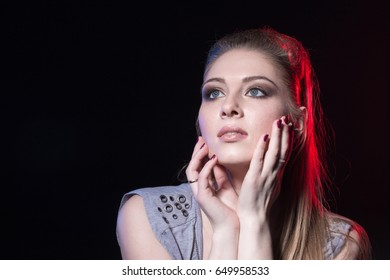 Portrait of actress in a grey dress on black stage after the performance