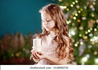 Portrait of acute long-haired little girl in dress on background of  lights.Little girl holding burning candle. Christmas, New Year and birthday celebration concept. Winter holidays. Copy space