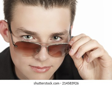 Portrait of adolescent boy taking off his sunglasses