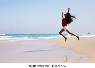 Portrait of adorable 12 years old girl jumping on the beach in summer day