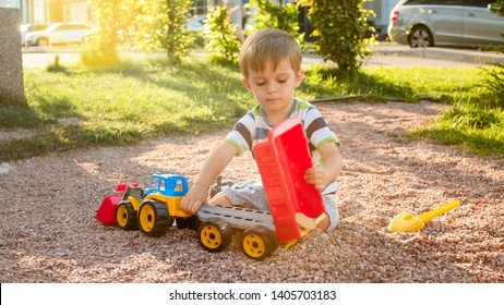 Portrait of adorable 3 years old toddler boy playing with toy truck with trailer on playground at park. Child digging and building from sand